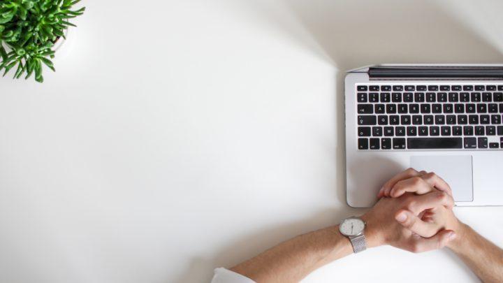 Mann sitzt vor Laptop mit gefalteten Händen