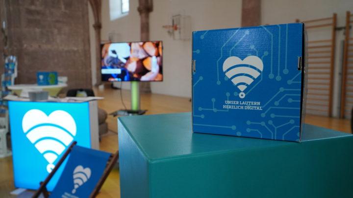 Stand von Unser Lautern - herzlich digital. Im Vordergrund ein Würfel mit dem Logo, im Hintergrund ein Monitor mit einem Video.