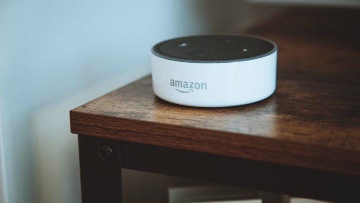Zu sehen ist ALEXA von Amazon auf einem braunen Tisch.