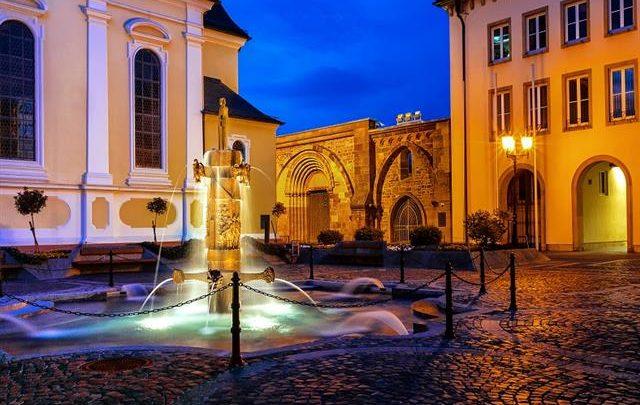 Zu sehen ist der Erkenbertbrunnen auf dem Rathausplatz in Frankenthal (Pfalz). Das Bild wurde bei Abend-Dämmerung aufgenommen.en