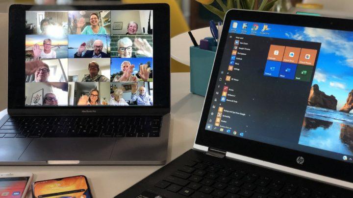Zu sehen ist ein Laptop (rechts auf dem Bild) auf dem die Windows Einstellungen gehöffnet sind und rechts ist ein Tablet zu sehen. Auf dem Tablet ist eine Konferenz geschaltet, in der 16 winkende Senioren zugeschaltet sind.