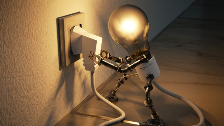 Zu sehen ist eine Glühbirne, deren Fassung Arme und Beine hat. Sie hält ihren eigenen in der Steckdose steckenden Stecker fest.
