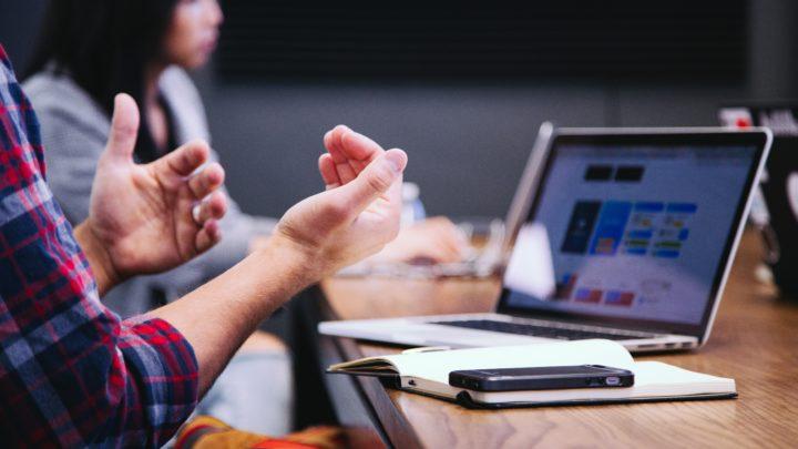 Zu sehen ist, auf der linken Seite, ein Hand der seine Hände gestikulierend bzw. erklärendvor sich hält. Von dem Mann ist nur der Oberkörper und die Hände zu sehen. Er spricht zu seinem Laptop, über diesen wohl eine Konferenz läuft.
