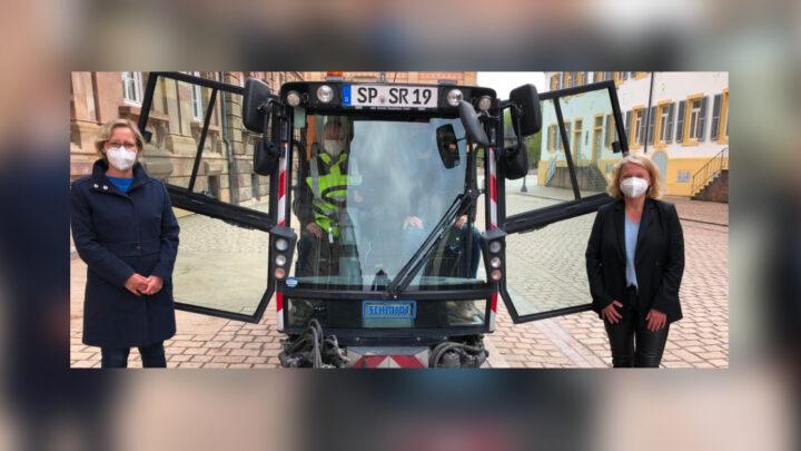 Zu sehen ist eine Kehrmaschine auf dem Domplatz in Speyer. Links nebendran steht Bügermeisterin Frau Seiler und rechts Frau Selg (Beigeordnete für Digitalisierung)