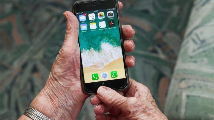 Seniorin hält ein Smartphone in der Hand