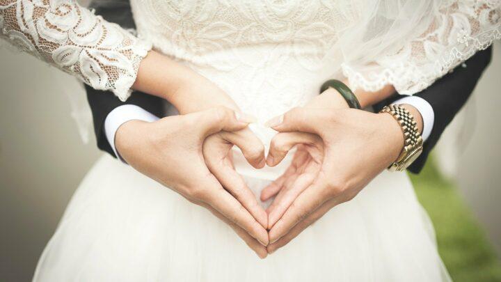 Zu sehen ist ein Brautpaar ohne Gesicht, die beide ein Herz mit ihren Händen formen.